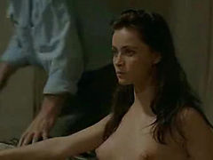Emmanuelle Beart removing her robe to reveal her fully nude body and then trying to pose in several different positions while a guy watches. She is giving us a nice look at her breasts, her butt and bush, and a brief peek between her legs. From La Belle N