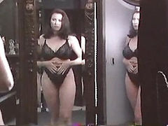 Mimi Rogers standing in front of a mirror in a black bra and panties as she takes off the bra and squeezes her large breasts together. We then see Mimi Rogers nude during a massage from a guy, and then flipping over as the guy kneads her very large breast