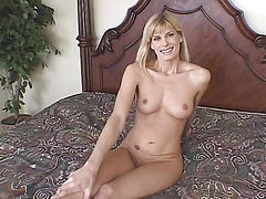 Girl blonde sitting nude on a big bed