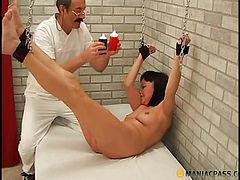 Mocks brunette pouring wax on her body