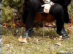 Bitch pees sitting down under a pine tree