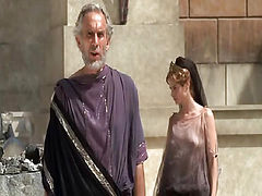 Sienna Guillory wearing a thin see-through purple top that shows us her breasts as she stands next to a guy in a courtyard. Then Sienna Guillory nude walking into a room, her nice butt on display as she walks through a crowd of people and steps onto a ped