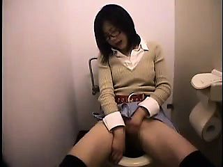 Horny Japanese babe with sexy legs sits on the toilet and m