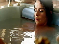 Crystal Allen reclining in the arms of Ana Alexander in a bath tub, her right nipple just barely coming into view above the water. From Femme Fatales.