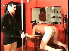 Horny mistress with big tits undresses and spanks her bending over slave hard on his ass with a wooden stick