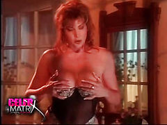 Lisa Comshaw removing her robe to reveal some lingerie and then taking that off and laying back on a chair and rubbing herself while looking at a guy before licking and sucking her fingers. She then rides the guy on a bed and has her breasts kissed before