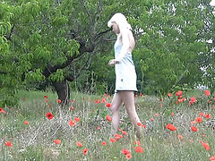 Splendid blonde teen taking off clothes in the field among the flowers on stream video.