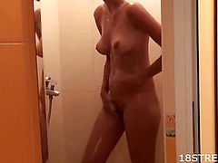 The girl holds the cock standing in the shower